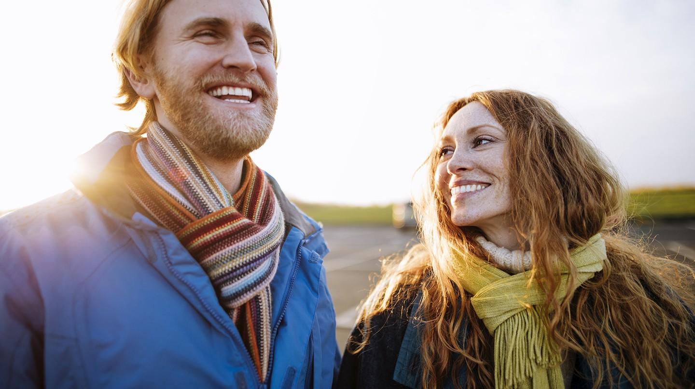 Ein junges Paar beim Spaziergang. Beide lächeln.