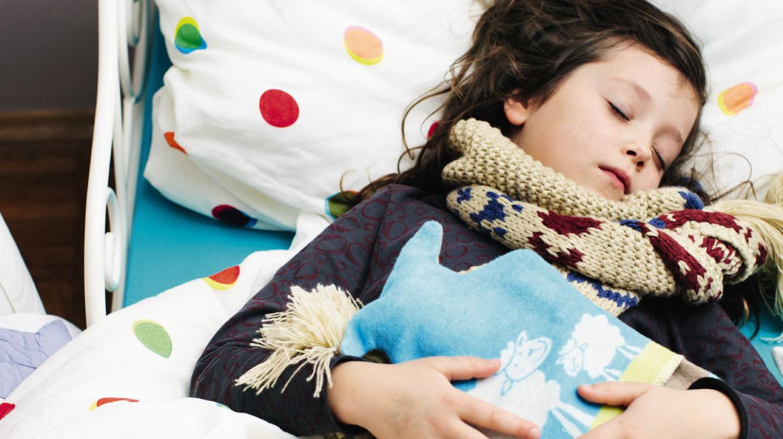 Erkältung bei Kindern: Mädchen mit Schal und Wärmflasche liegt schlafend im Bett