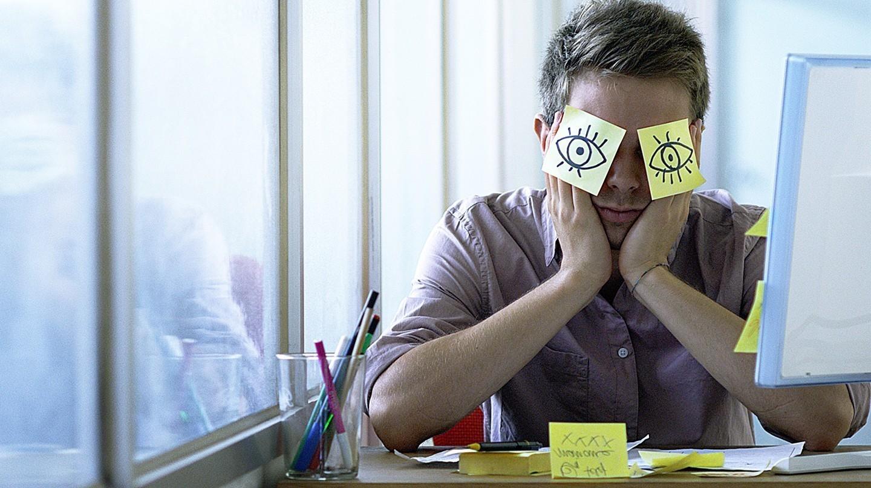 Symbol für Schlafstörungen durch Homeoffice: Ein junger Mann sitzt vor einem Computer. Auf seinen Augen kleben zwei Post-its, auf die offene Augen gemalt sind.
